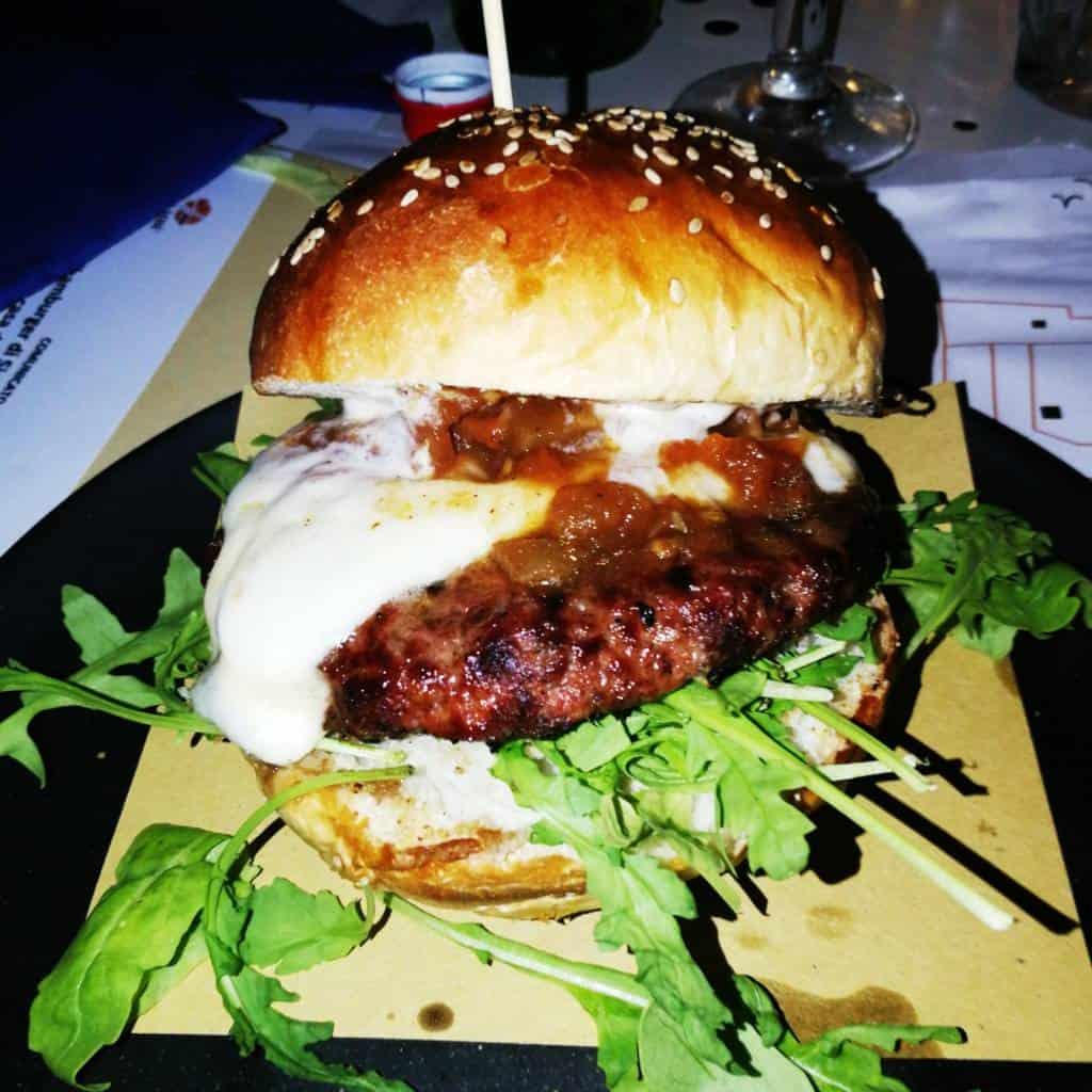 Nel menu di 'Zzambù, pizzeria burgeria sul lungomare di Napoli, da qualche tempo si trova lo 'Zzamburger, un panino nato dall'inventiva Antonio Di Sieno, macellaio da quattro generazioni.