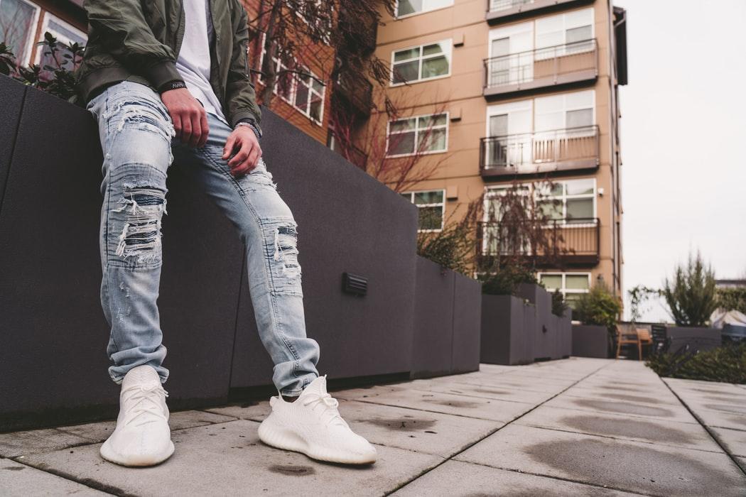 Felpa sporty con cappuccio e short jeans per lui, jeans sdruciti e gambe a vista per lei: è la foto che li ritrae insieme, è lo Street Style